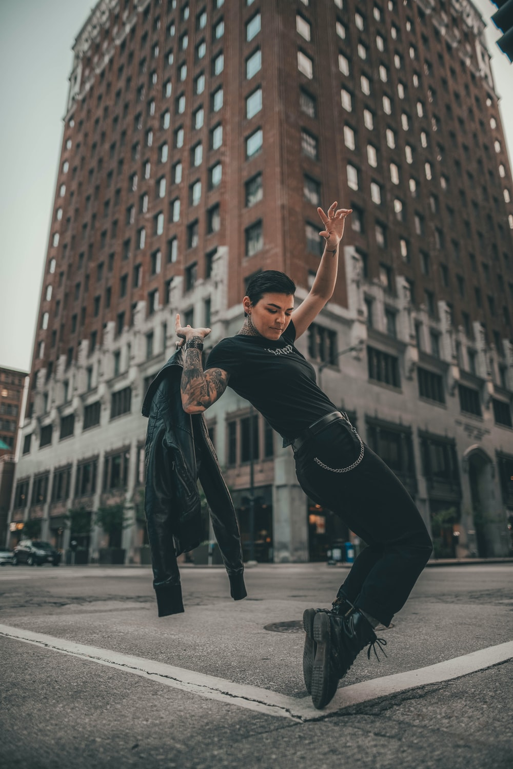 man in black t-shirt and black pants jumping on gray concrete floor during daytime