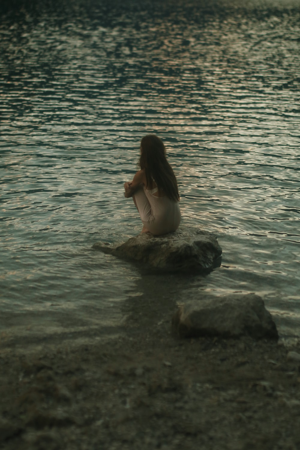 woman in white tank top sitting on rock in the sea during daytime