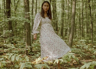woman in white and black floral dress standing in the woods