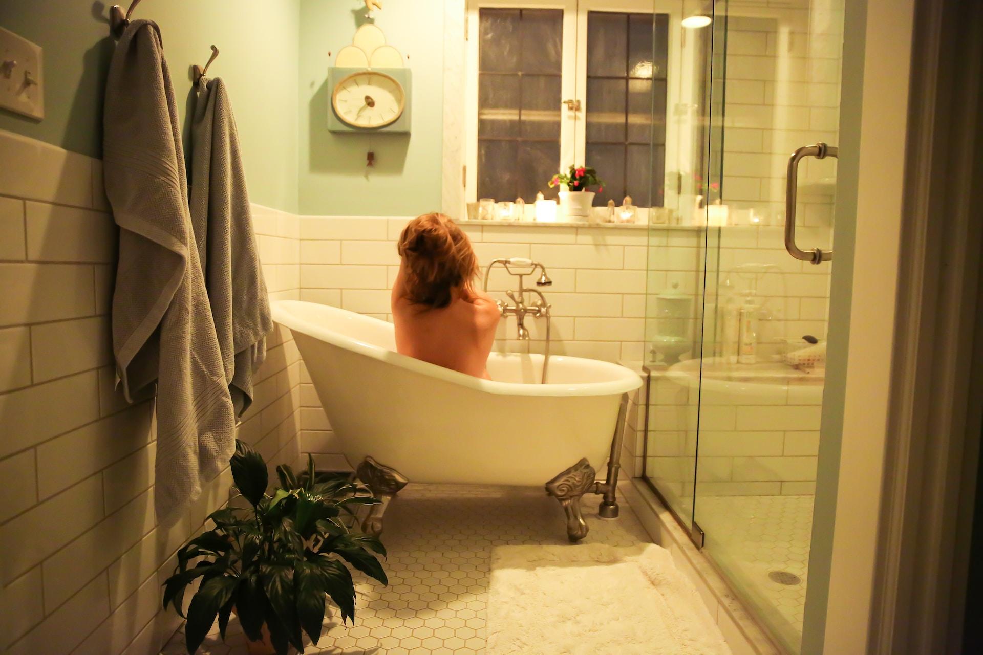 woman in bathtub near white bathtub