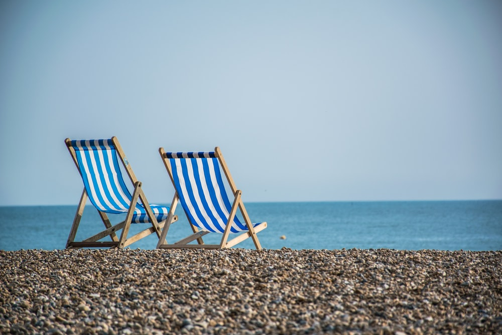 blue and white striped folding chair on beach during daytime
