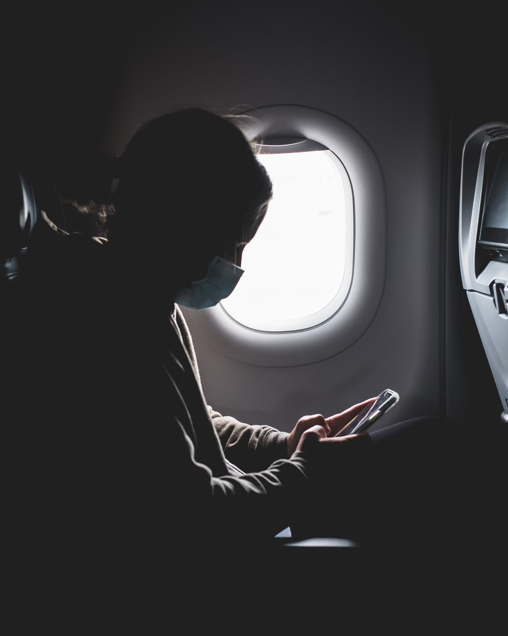 woman in black long sleeve shirt sitting on airplane seat