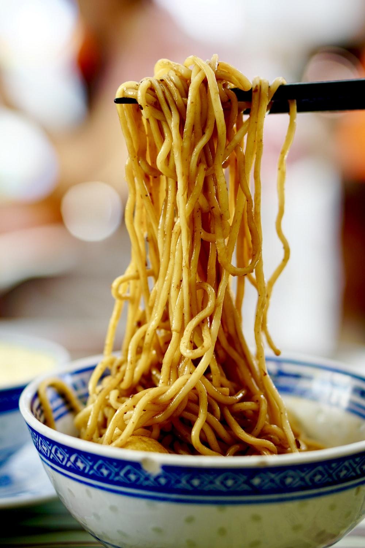 yellow pasta on blue and white ceramic bowl