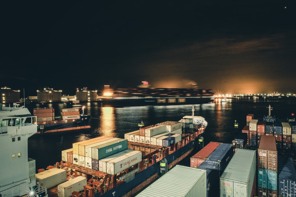 blue and red cargo ship on dock during night time