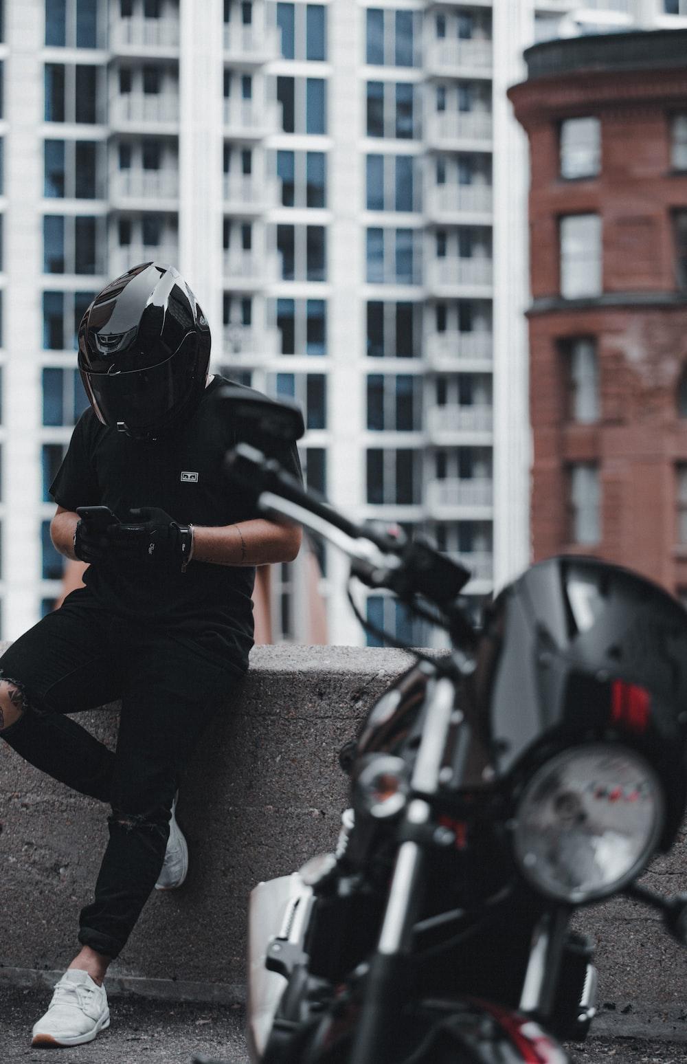 man in black jacket and gray pants wearing black helmet riding motorcycle during daytime