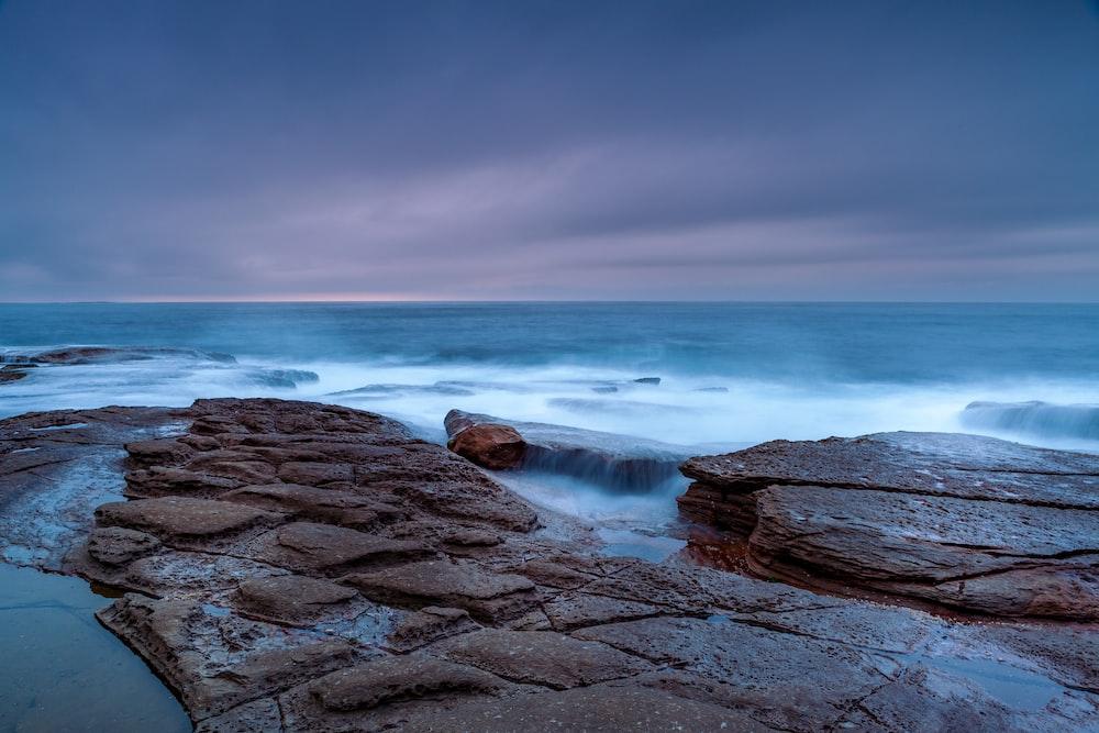 brown rocky shore near ocean water under blue sky during daytime