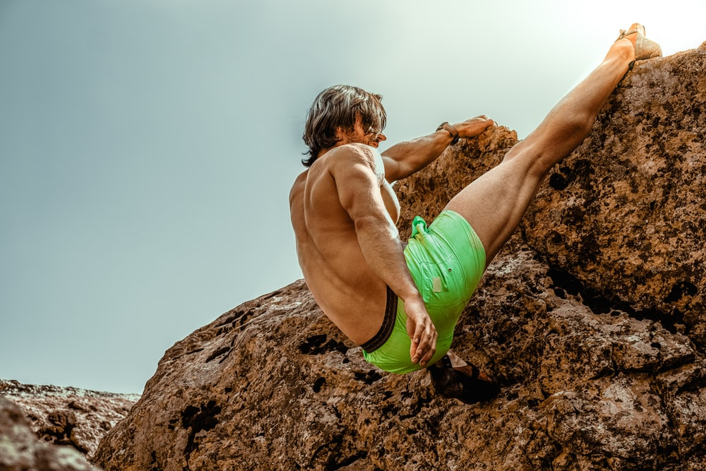 boy in green shorts climbing on brown rock during daytime