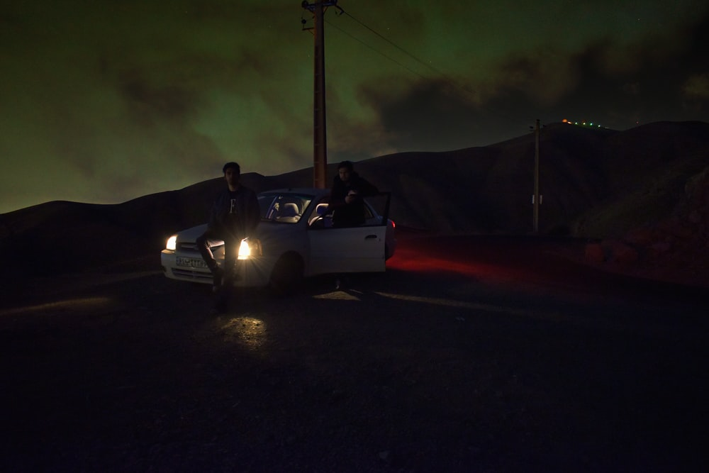 man in black jacket riding white coupe during night time