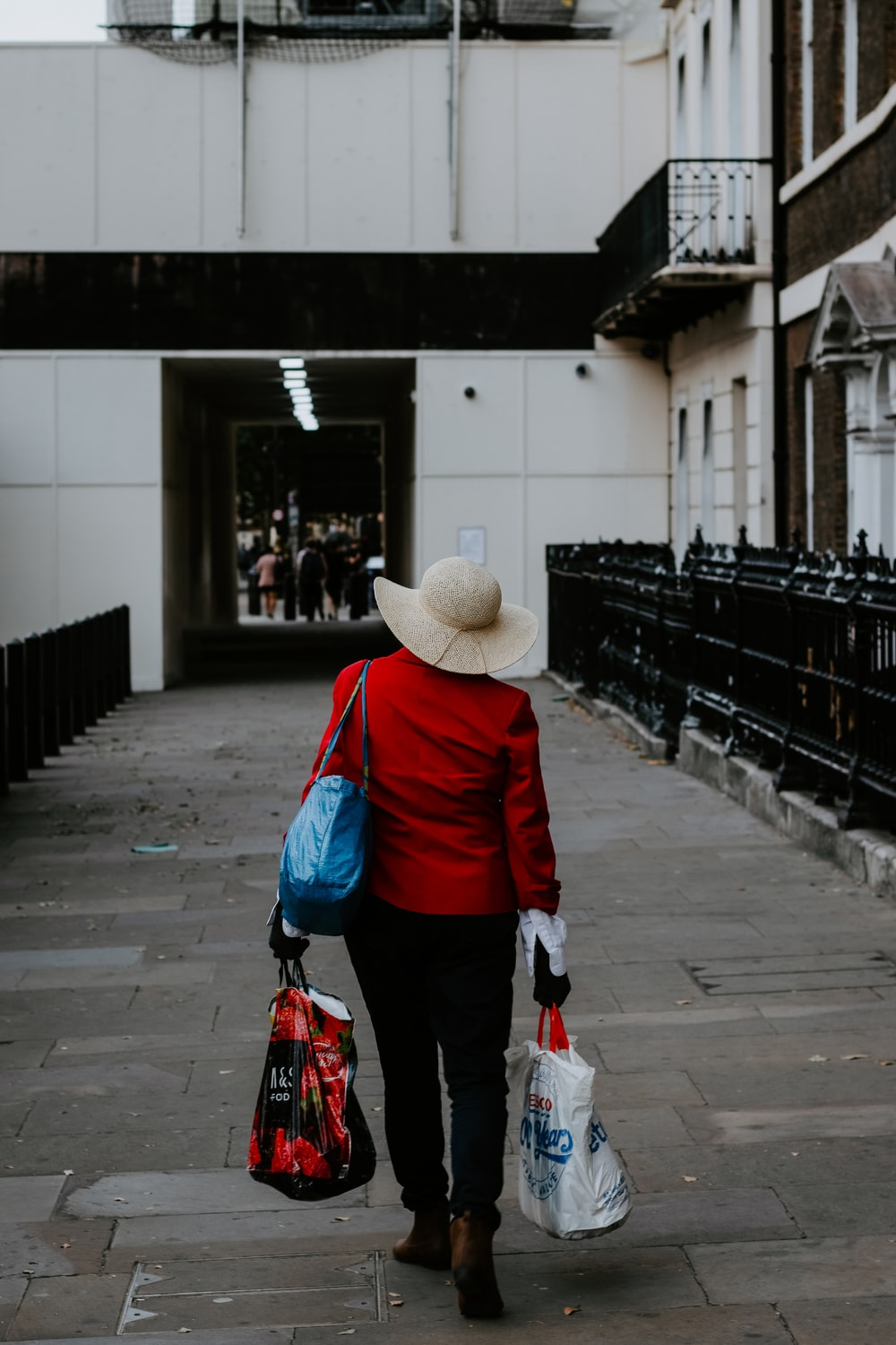 person in red jacket and black pants wearing brown hat walking on sidewalk during daytime