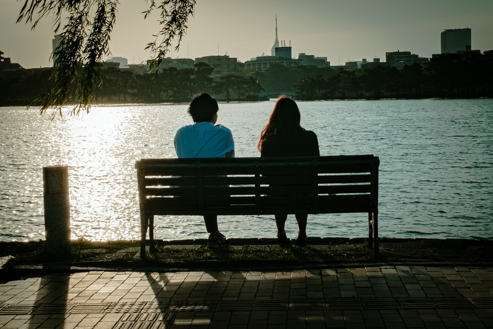 2 person sitting on bench near body of water during daytime