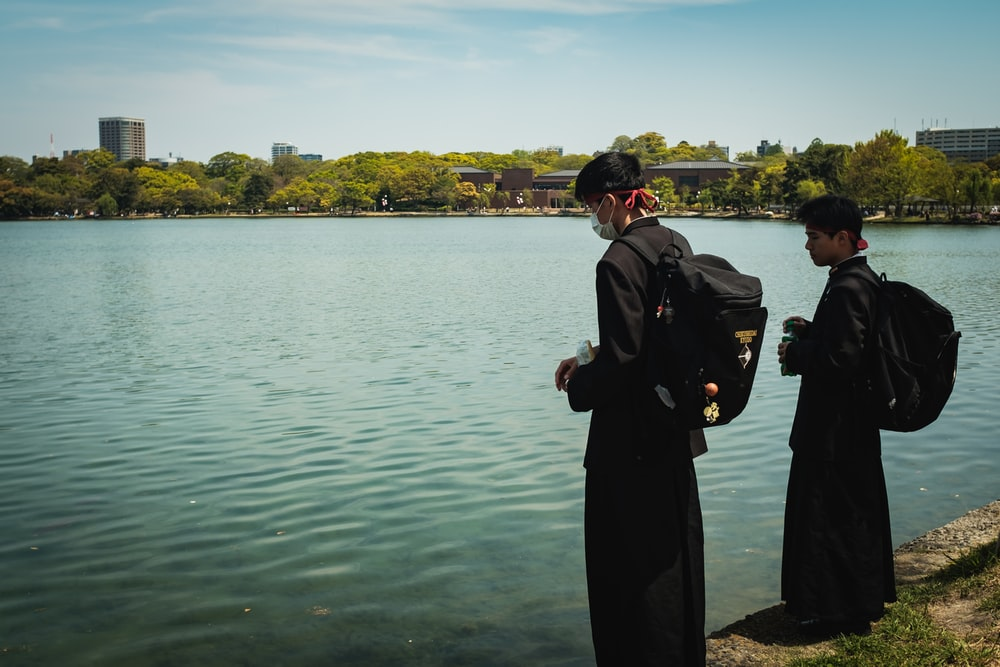 man in black coat standing near body of water during daytime