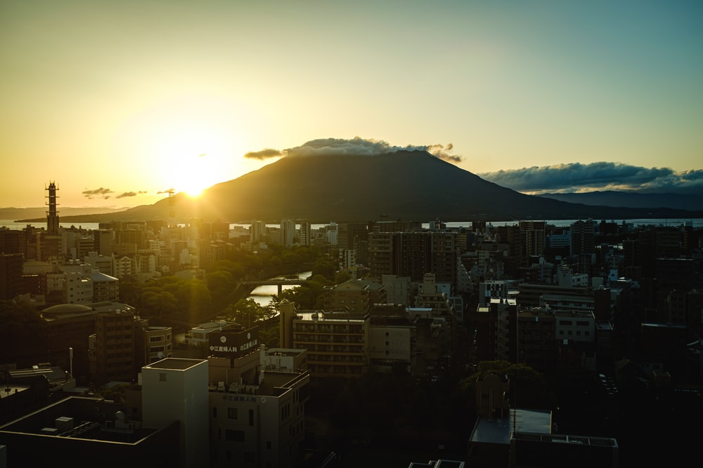 city with high rise buildings near mountain during sunrise