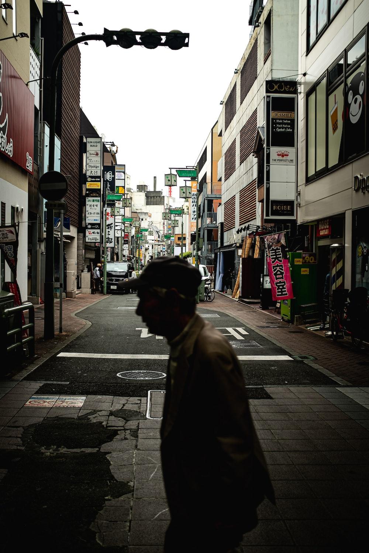 man in black coat walking on sidewalk during daytime
