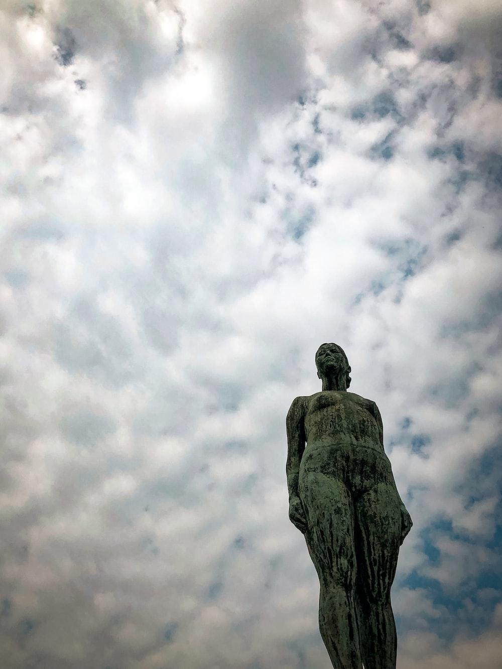 man statue under white clouds during daytime