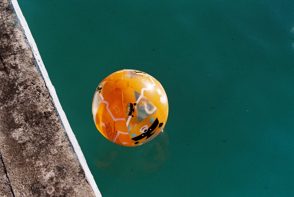 yellow and white balloon floating on water