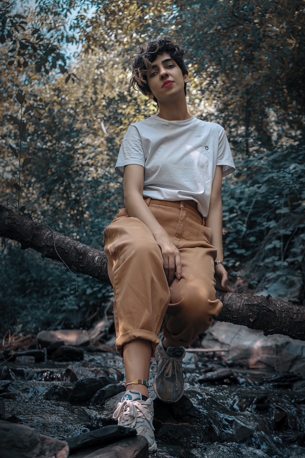 woman in white crew neck t-shirt and brown pants sitting on tree branch during daytime