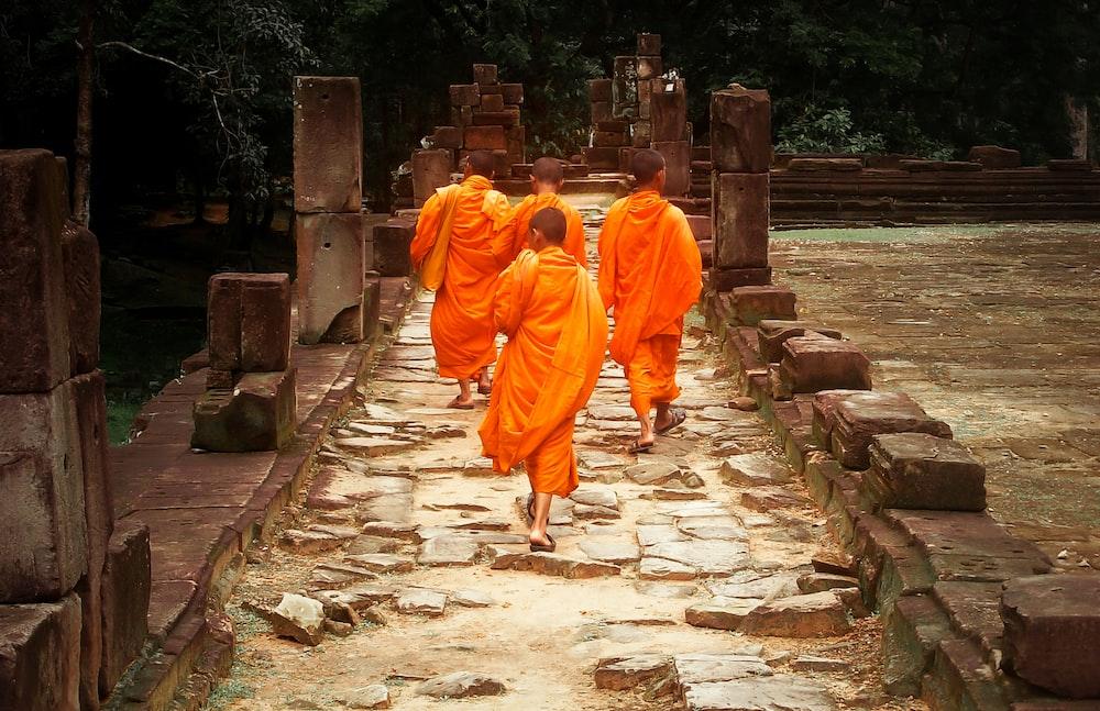 man in orange robe walking on gray concrete pathway during daytime