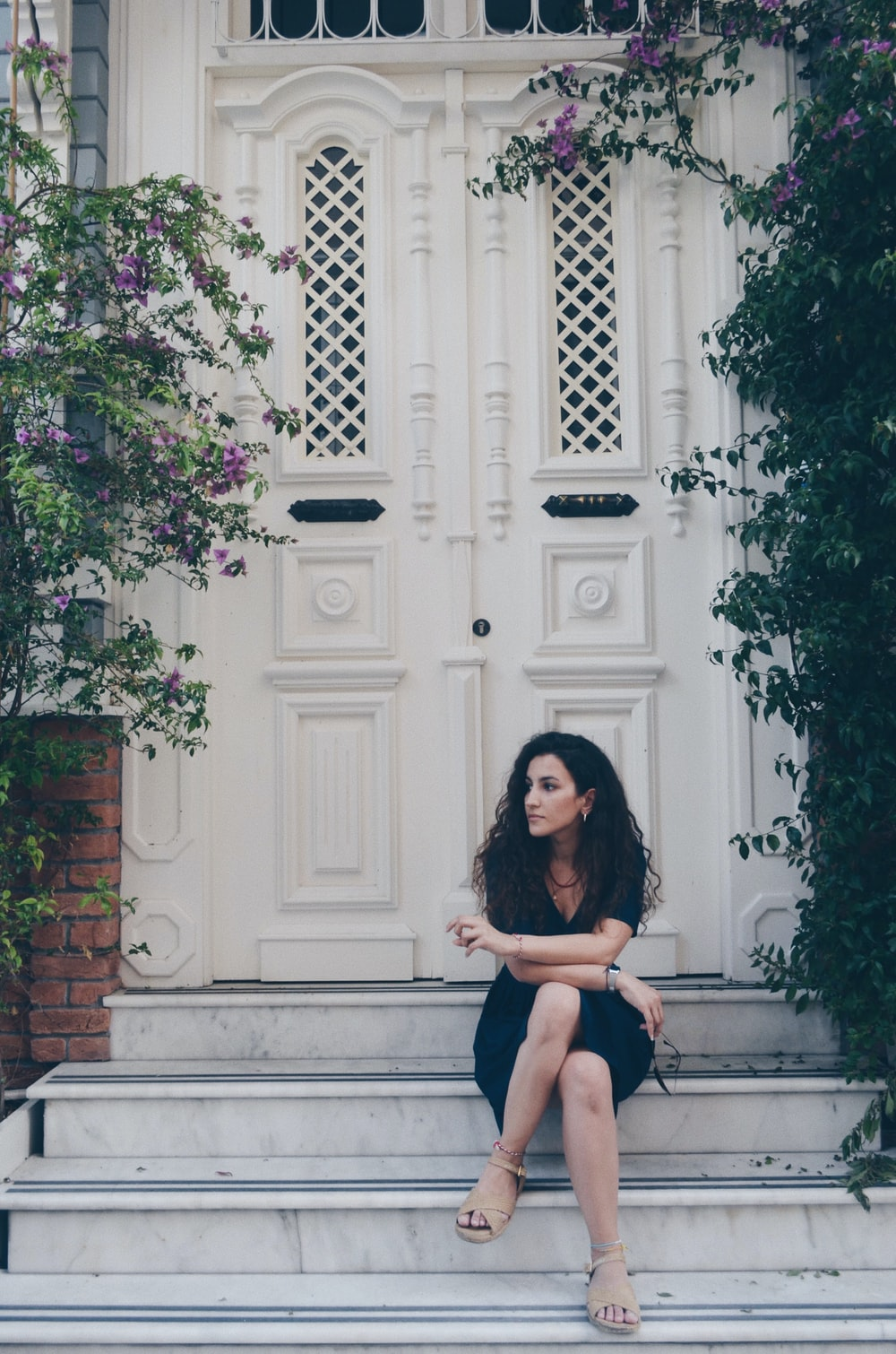 woman in black dress standing near white wooden door
