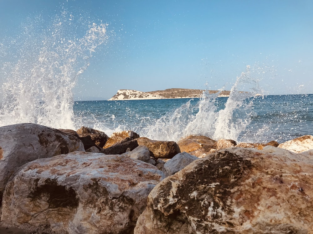 brown rocky shore with ocean waves crashing on shore during daytime