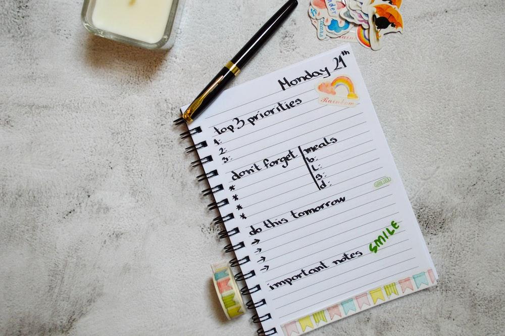 black pen on white notebook
