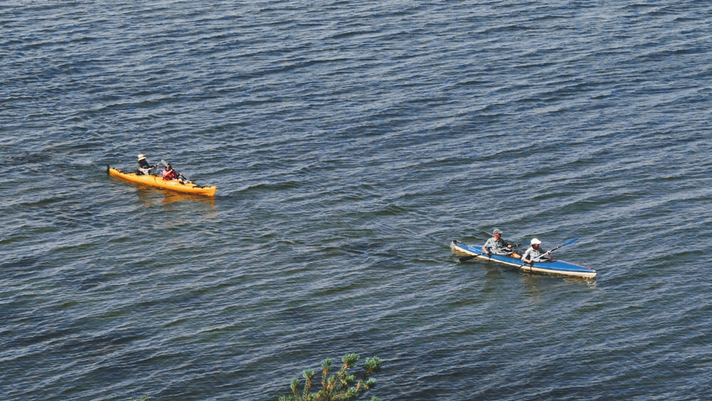2 people riding on yellow and white kayak on body of water during daytime