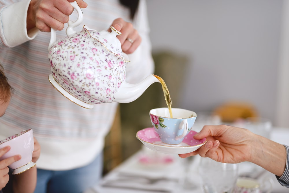 person holding white and pink floral ceramic teapot