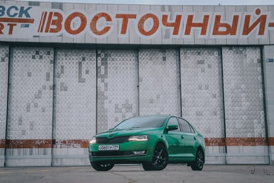 green sedan parked beside gray concrete wall skoda teams background