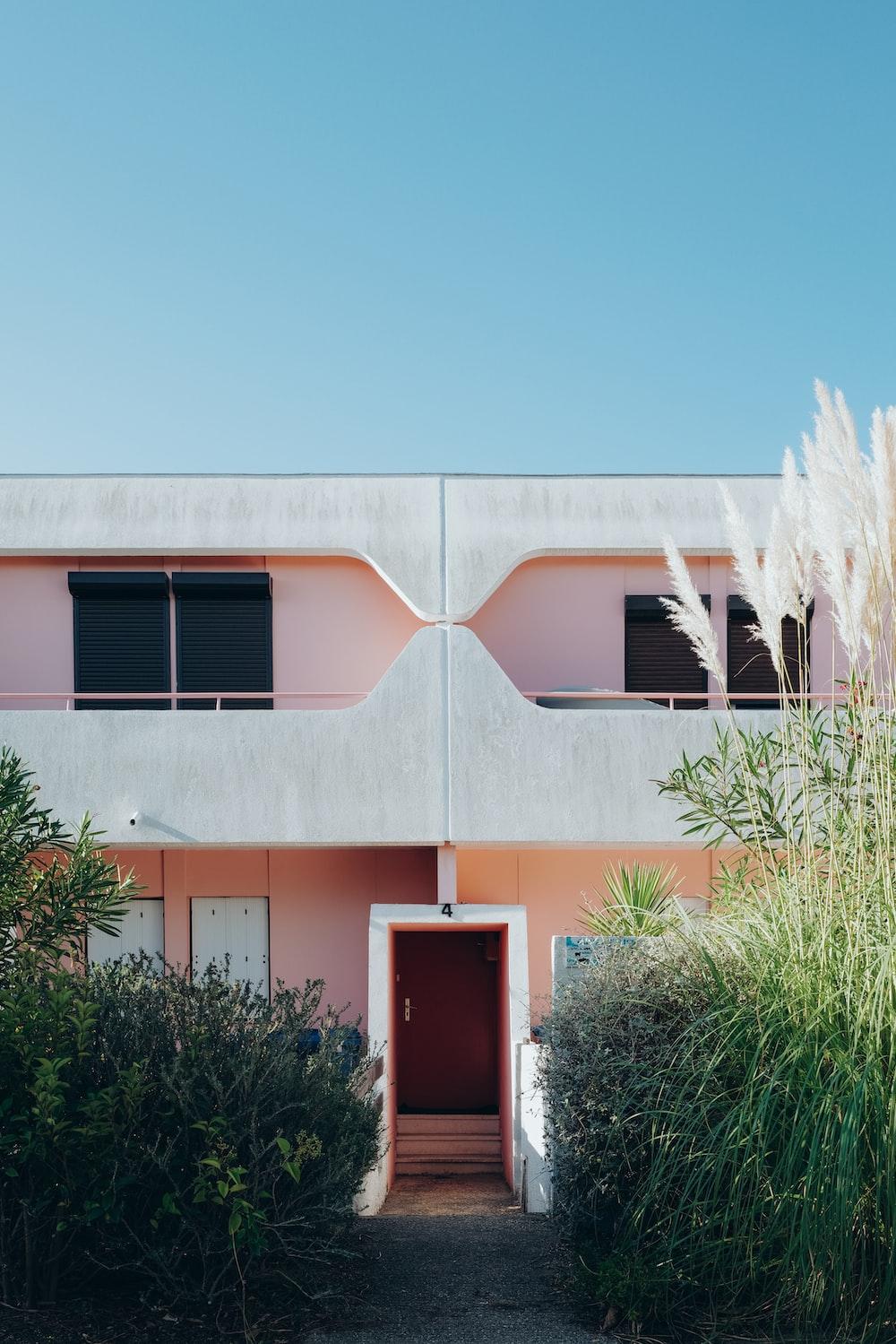 green plants beside pink concrete house