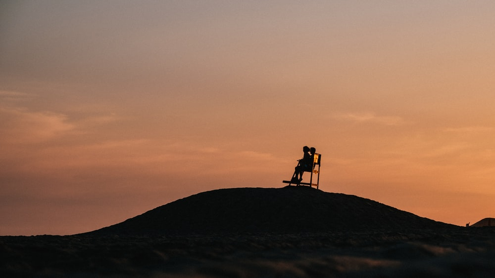 silhouette of 2 people standing on top of mountain during sunset