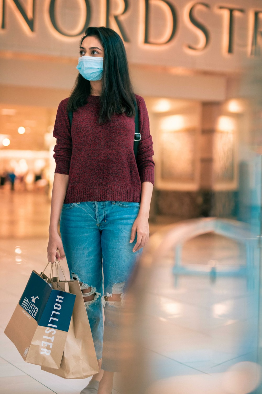 woman in red long sleeve shirt and blue denim jeans holding blue shopping bag