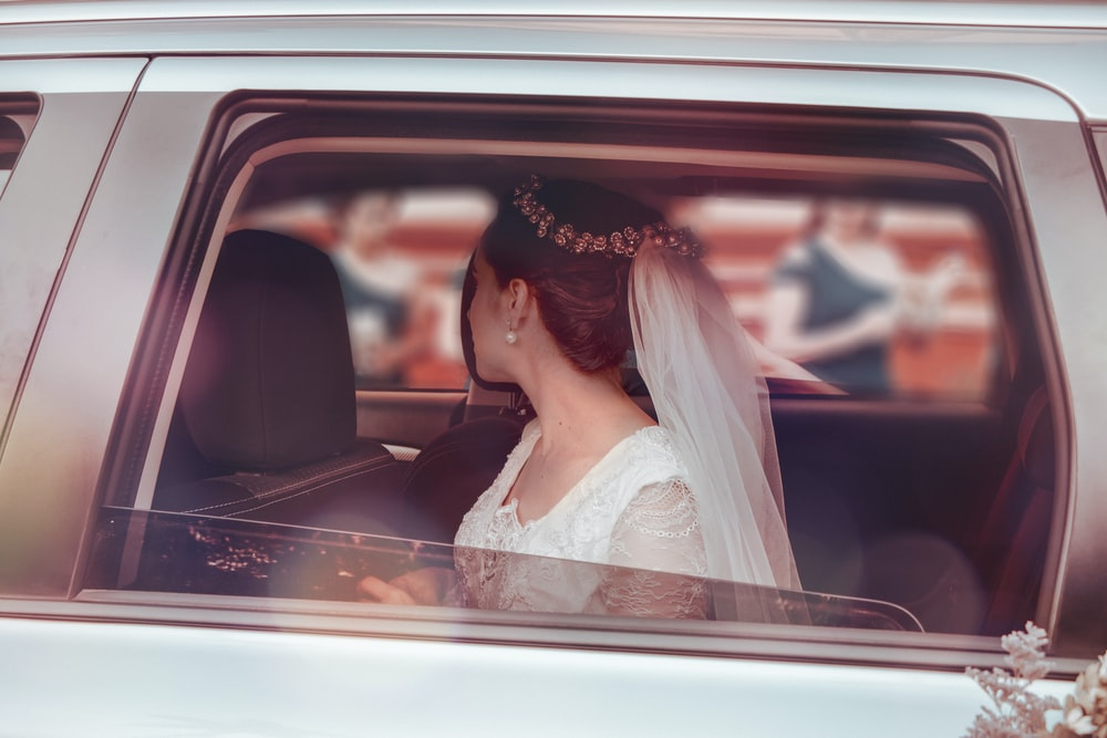 woman in white wedding gown sitting on car seat