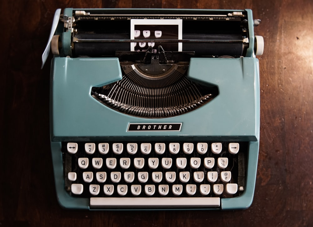 green and black typewriter on green table