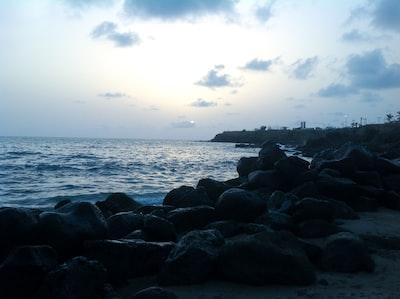 black rocks near body of water during daytime