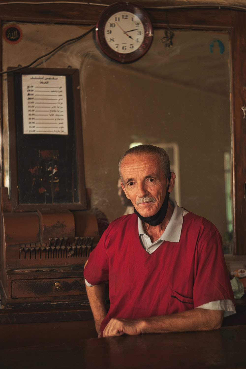 man in red polo shirt standing beside brown wooden piano