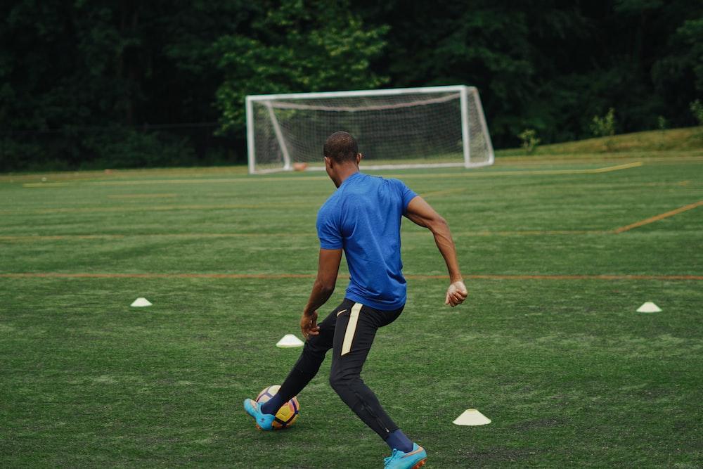 man in blue shirt playing soccer during daytime