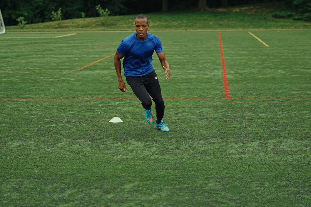 man in blue nike crew neck t-shirt and black pants running on green grass field