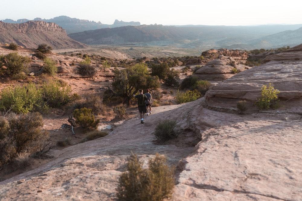 man in black jacket walking on brown rocky mountain during daytime