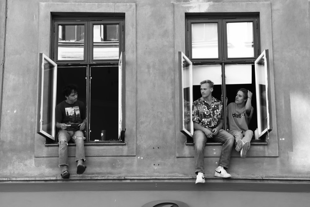 grayscale photo of 2 men and 2 women sitting on window