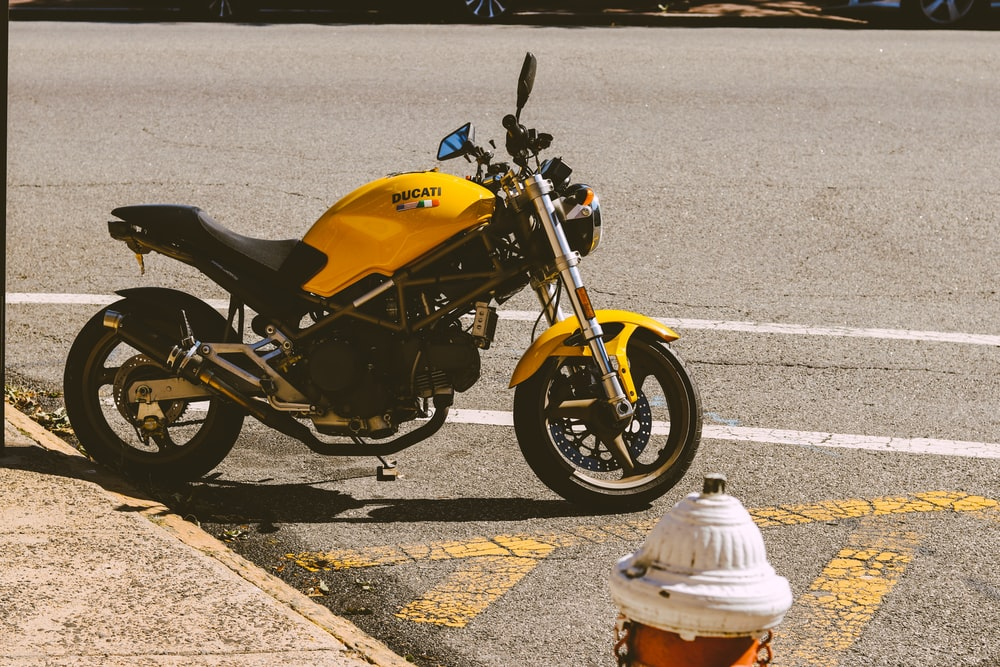 yellow and black sports bike parked on gray concrete road during daytime