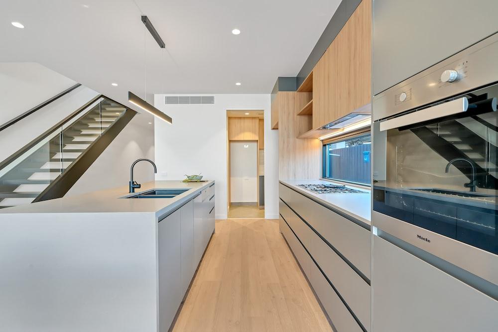 brown wooden parquet floor and white wooden kitchen cabinet