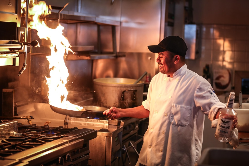 man in white chef uniform cooking