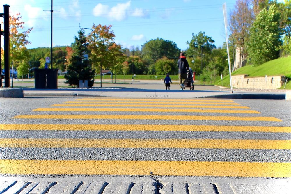 2 person walking on pedestrian lane during daytime