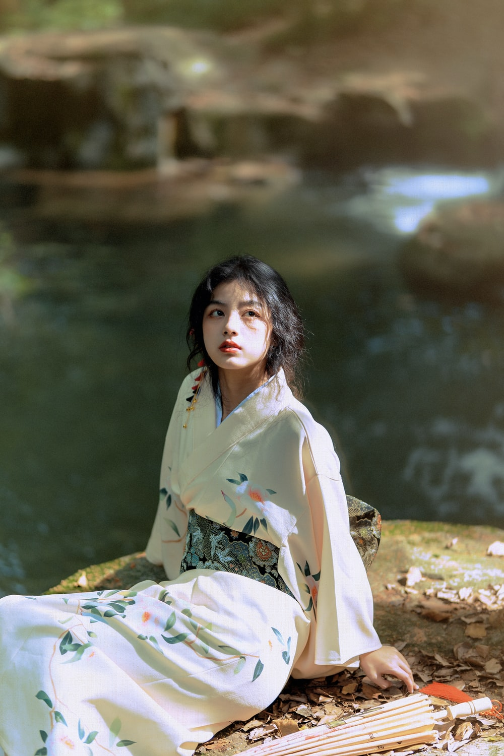 woman in green and white floral kimono sitting on rock near river during daytime