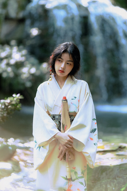 woman in white kimono standing near white flowers during daytime