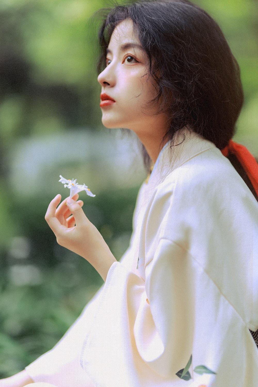 woman in white long sleeve shirt holding white flower