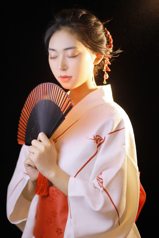 woman in white long sleeve shirt holding hand fan