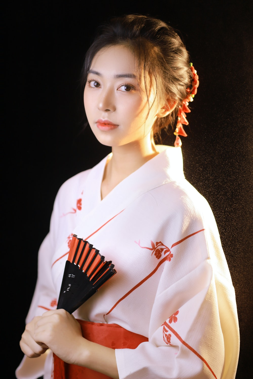 woman in white robe holding hair comb