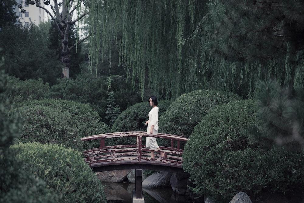 woman in white dress standing on brown wooden bridge