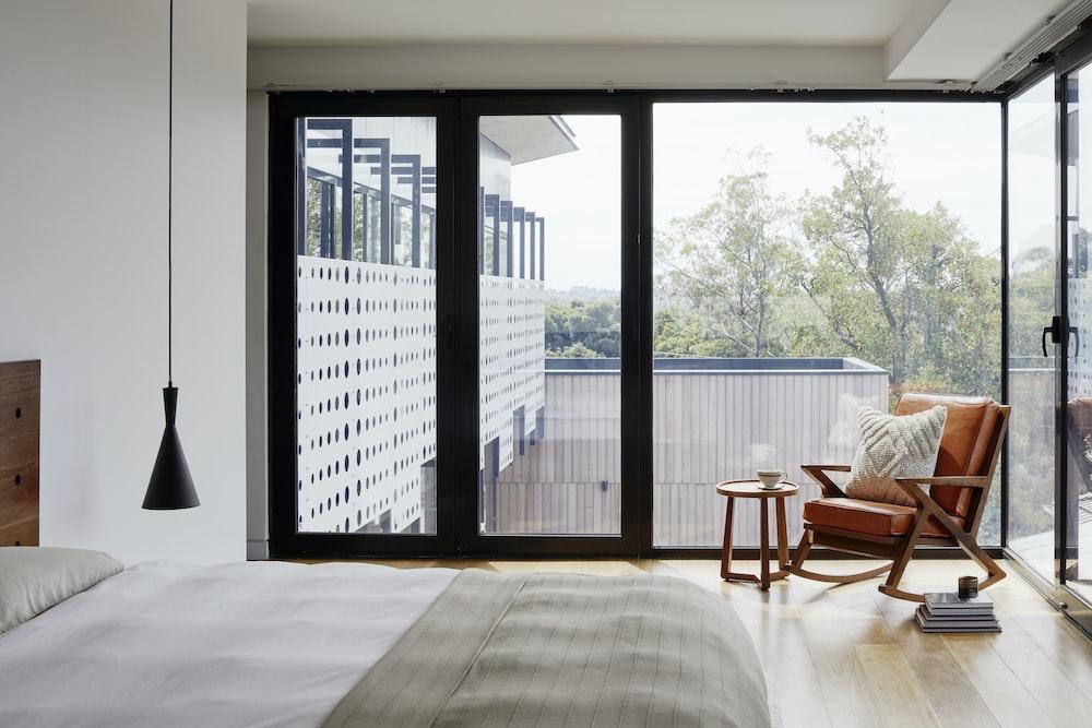 brown wooden armchair near glass window