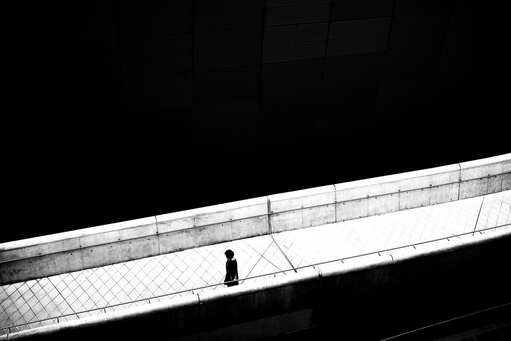 person in black jacket walking on white concrete bridge
